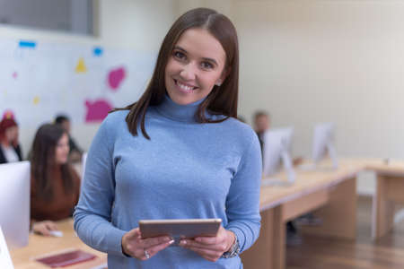 Portrait of a pretty cheerful casual turkish girl holding tablet or ipad inside modern computerlab classroom. Technology and education concept Standard-Bild