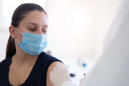 vacine injection by doctor at hospital.Doctor making injection vaccination patient to prevent pandemic of the disease, flu or influenza virus in clinic Standard-Bild