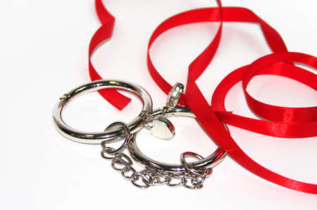 Metal handcuffs isolated on the white background and red ribbon photo