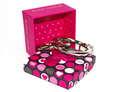 Metal handcuffs with gift box isolated on the white background photo