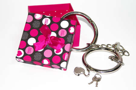 bdsm handcuff: Metal handcuffs with gift box isolated on the white background Stock Photo