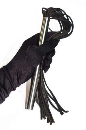 Black fetish flogging whip in woman hand Stock Photo