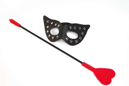 flogging: Black leather mask with metal rivets and red crop isolated on white Stock Photo