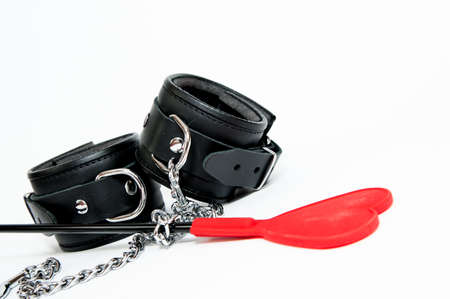 Black handcuff and flogging whip Stock Photo