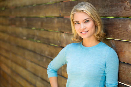 Beautiful blonde woman portrait smiles next to wood fence