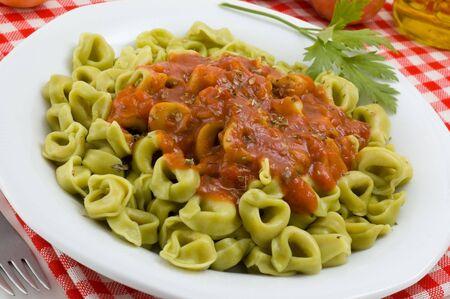tortellini: Italian tortellini with tomato sauce. Stock Photo