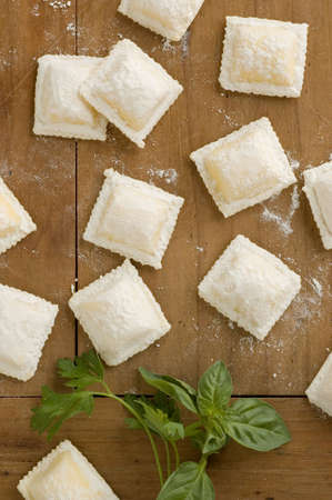 italian ravioli with basil and parsley on table