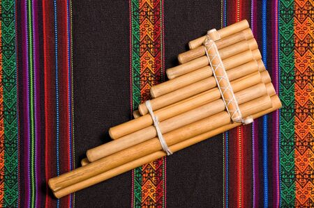 andean: siku, andean wind musical instrument, on traditional tapestry.