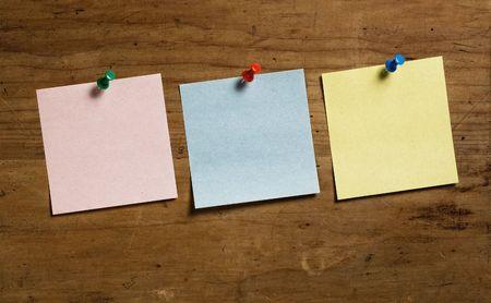 tack board: Tres Notas con Tack sobre tabla de madera, en tres colores diferentes.