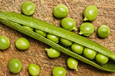 Fresh green peas on wooden background, studio shot.