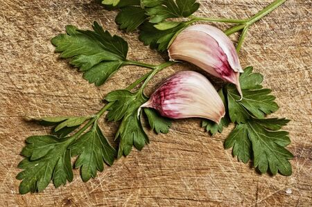 garlics: Garlic and parsley isolated on wooden background.