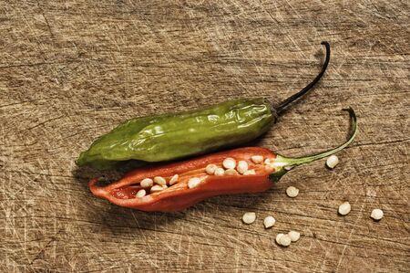 spicey: Due Chili Peppers su una tavola di taglio.