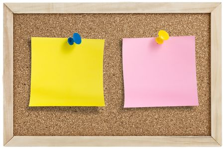 Yellow and pink remainder notes on cork board, with tacks. photo