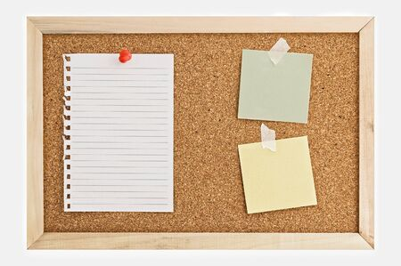 Cork Pin Board  with a sheet of paper, post it notes, and thumbtacks. Stock Photo
