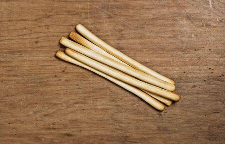 oj: Bunch oj Bread sticks on a wooden table.