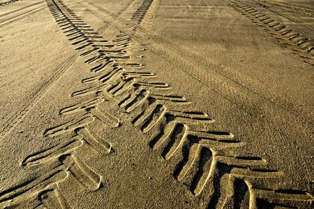 Tractor and car tracks in the sand at dusk. photo