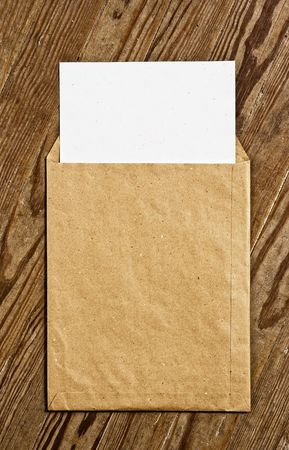old envelope: Open Brown Vintage Envelope, with white paper, over wooden surface. Stock Photo