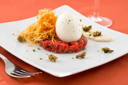Gourmet dish with egg and raw meat. Studio shot. photo