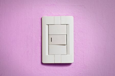 White light switch on old pink wall. photo