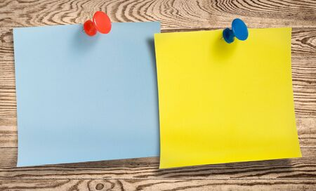 Two note papers with thumbtacks in wooden surface. photo