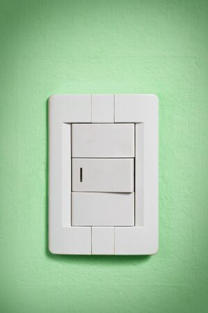 White light switch against a green wall. photo