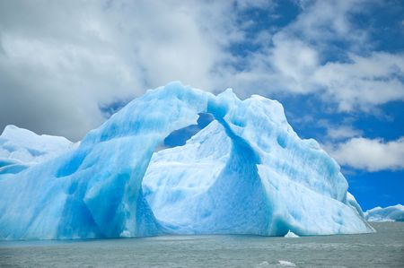 Iceberg floating in the water forming an arch.