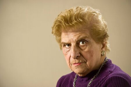 living wisdom: Depressed old woman staring at the camera. Stock Photo