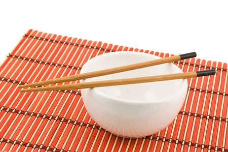 Chinese chopsticks and bowl on red bamboo mat. photo