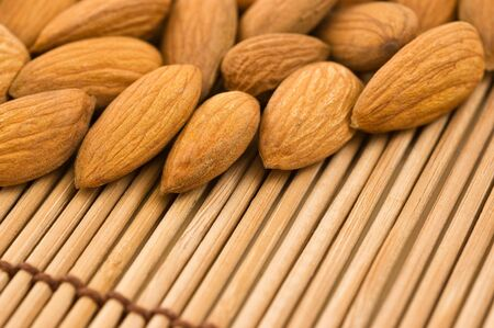 Group of almonds on a bamboo mat, close up. photo