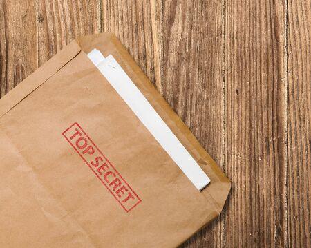 최고 비밀 스탬프와 논문, 나무 테이블에 열려있는 노란색 봉투
