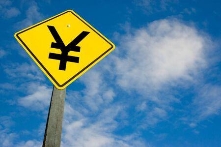 Yen symbol on a yellow traffic sign. photo