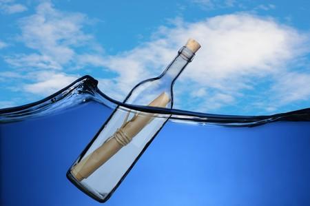 Boodschap in een fles drijvend op de golven.  Stockfoto