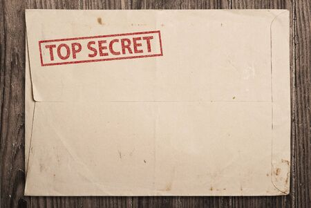 Open yellow envelope with top secret stamp and papers, on wooden table Stock Photo - 8076502