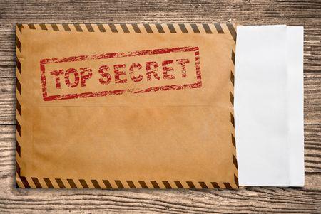 Open gele envelop met top geheime stempel en leeg papier, op houten tafel  Stockfoto