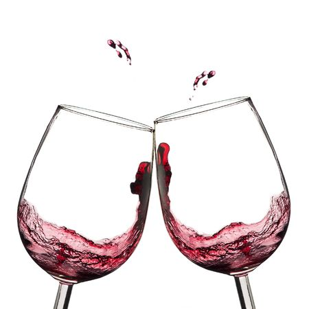 Two wine glasses in toasting  with splash.