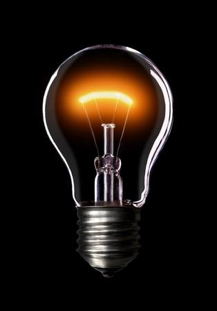 Light Bulb eingeschaltet, schwarzer Hintergrund. Standard-Bild