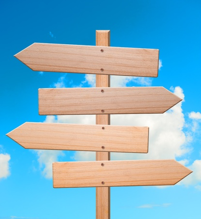 Arrow signs made out of wood isolated, with sky in background and clipping path.