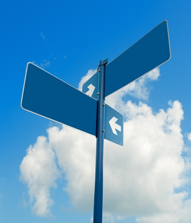 Blank blue road signs in bright sky