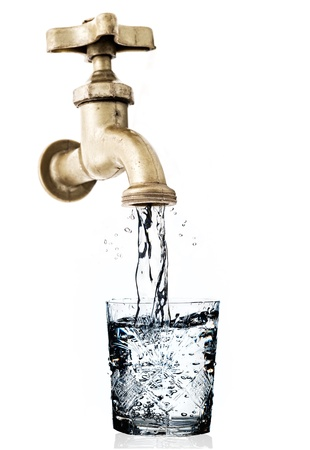 Tap, with flowing water and glass, isolated,  white background.
