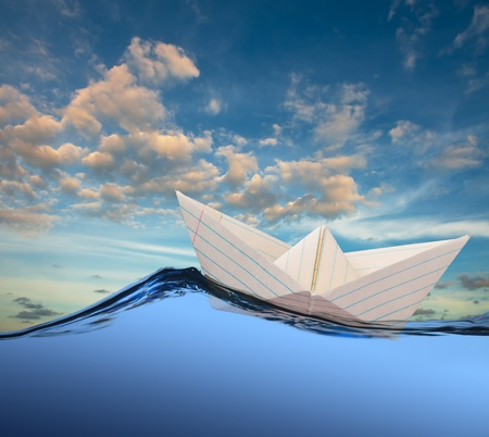 drift: White paper boat floating in the sea.