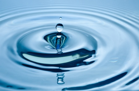 Vallende druppel water op blauw.