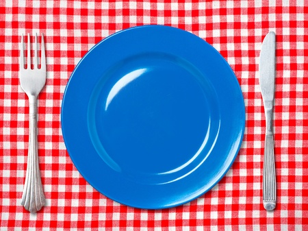 Empty blue dinner plate with fork and knife on red and white checked tablecloth. photo