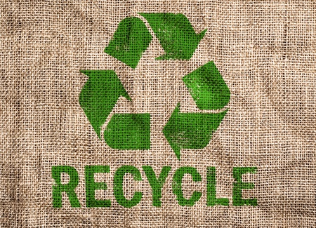 sack cloth: Rough old canvas with green recycle sign.  Stock Photo