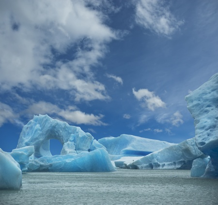 Iceberg floating in the water forming an arch. El Calafate, Argentina.  photo