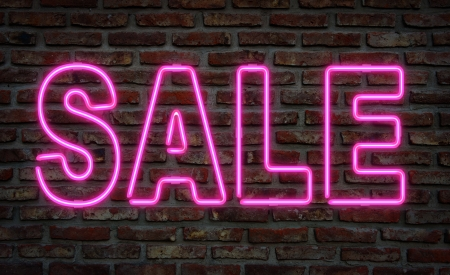 illuminated wall: Glowing neon sale sing on a brick wall. Stock Photo