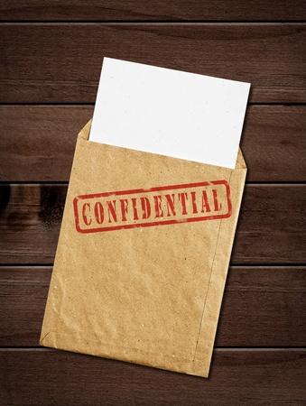 Open gele envelop met top geheime stempel en documenten, op houten tafel, het knippen weg.