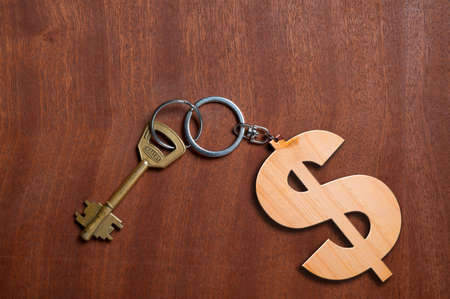 key in chain: Money concept with key chain on wooden table.