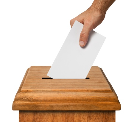 Hand putting a blank voting ballot into the box isolated on white background, clipping path. photo