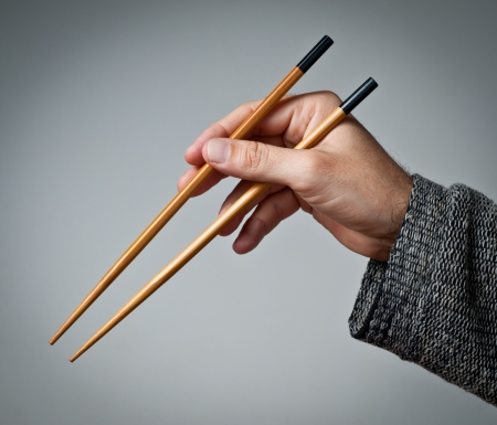 chop stick: Male hand with chinese chopsticks.  Stock Photo