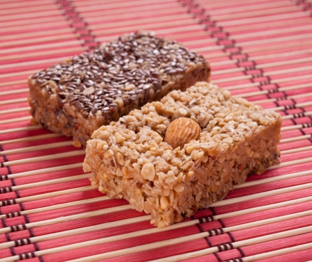 Homemade flapjack with almonds and seed on red mat. photo